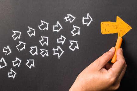 lideres: Gráfico de la mano de naranja flecha como líder de tendencia con muchas flechas blancas como seguidor