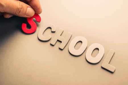 arrange: Hand arrange wood letters as School word