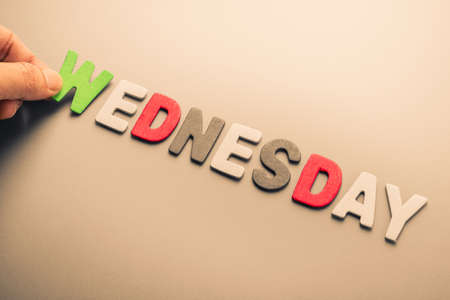to arrange: Hand arrange wood letters as Wednesday word