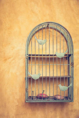 vintage objects: Vintage bird cage decorated on the wall, Tuscan style house