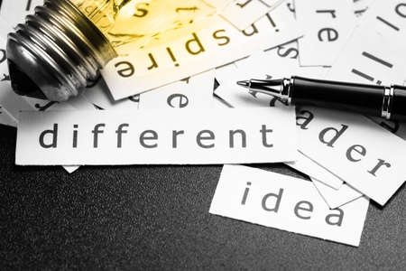 specialize: Pile of inspiration words printed in pieces of paper with light bulb and pen, closeup at Different word