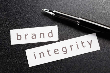 integrity: Brand Integrity word in piece of paper with pen on black background