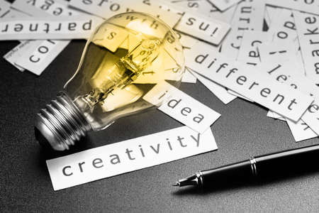 specialize: Pile of inspiration words printed in pieces of paper with light bulb and pen, closeup at Creativity word