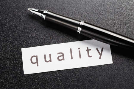 pen quality: Quality word in piece of paper with pen on black background