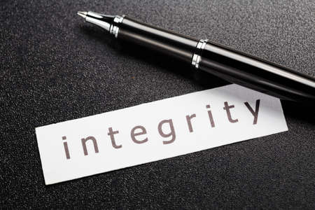 morale: Integrity word in piece of paper with pen on black background Stock Photo