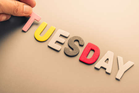 arrange: Hand arrange wood letters as Tuesday word