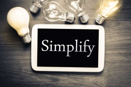 simplify: Simplify topic in mobile tablet with many light bulbs on wood table