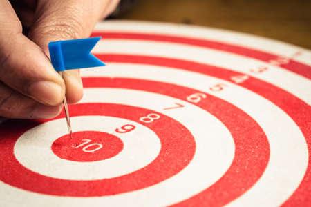 Closeup hand going to put a flag push pin into the center of dartboard 免版税图像