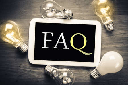 FAQ (Frequently Asked Question) topic on mobile tablet with glowing light bulbs on the table Stockfoto