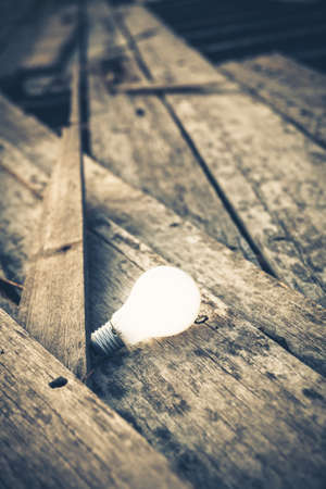 glowing: Usable Idea, Light bulb still glowing on pile of old planks Stock Photo