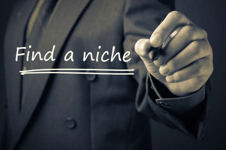 specialize: Businessman write Find a Niche on Screen Stock Photo