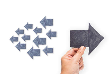 differentiation: Hand hold a paper arrow to opposite direction from others Stock Photo