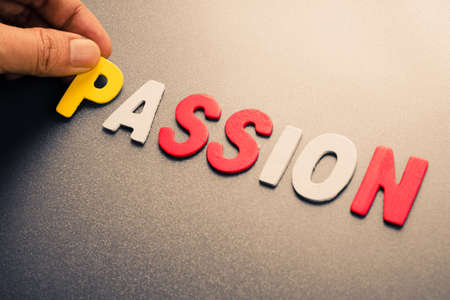 to arrange: Hand arrange wood letters as Passion word Stock Photo