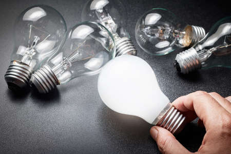 brighter: Hand take a white light bulb that glowing brighter than another one Stock Photo