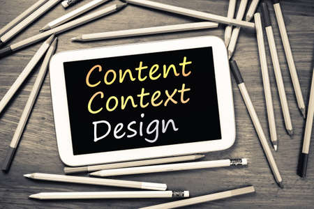 context: Content, Context and Design (CCD) on mobile tablet with many pencils Stock Photo