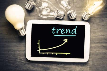 trending: Trending graph on mobile tablet with many light bulbs