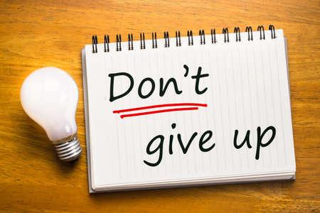 give up: Dont Give Up text as memo on notebook with light bulb