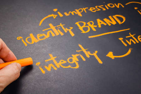 Hand writing Brand concept on chalkboard, focus at Integrity word