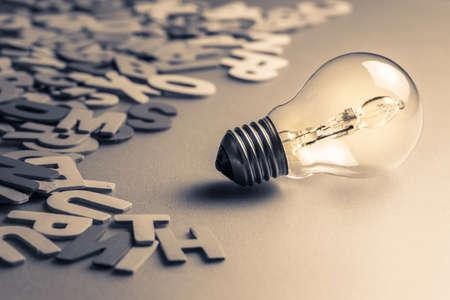 Ampoule et lettres de bois dispersés Banque d'images