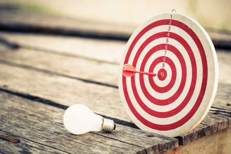 dart on target: Dart hit the center of dartboard with light bulb