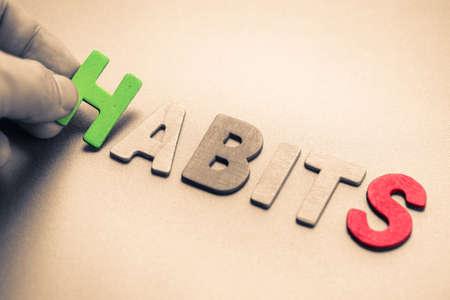 to arrange: Hand arrange wood letters as Habits word