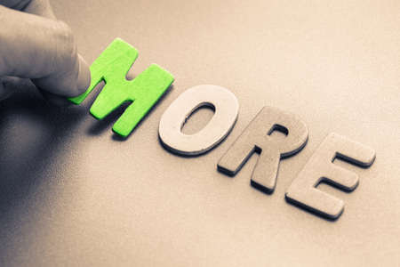 arrange: Hand arrange wood letters as More word Stock Photo