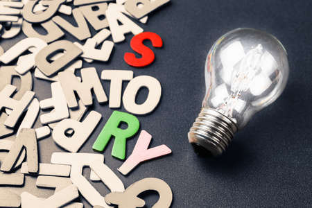 story: Light bulb and scattered wood letters as creative story telling for branding or awesome content concept