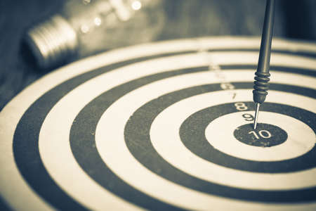 dart on target: Smart goal setting, dart hit the center of dartboard with light bulb on background Stock Photo