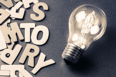 Light bulb and scattered wood letters as creative story telling for branding or awesome content concept