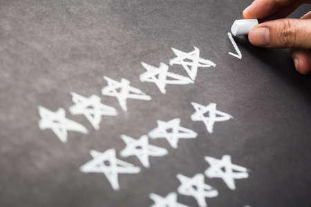 Closeup hand mark five stars rating on chalkboard