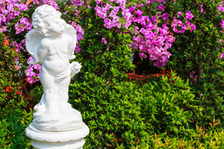 bougainvilleas: Cupid statue in the garden with bougainvilleas flower Stock Photo