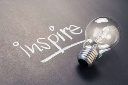 Handwriting of inspire word with glowing light bulb Stock Photo