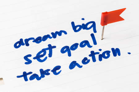 push pin: Dream Big, Set Goal, Take Action as memo on notebook with flag push pin