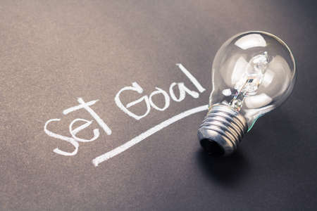 set goal: Handwriting of Set Goal text with glowing light bulb