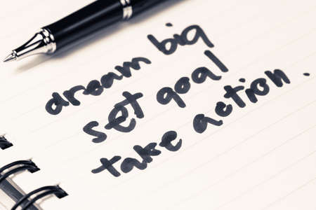 take action: Dream Big, Set Goal, Take Action as memo on notebook