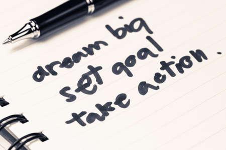 set goal: Dream Big, Set Goal, Take Action as memo on notebook