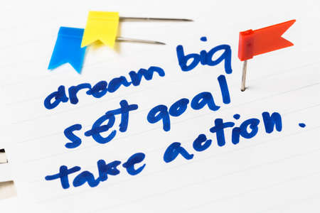 set goal: Dream Big, Set Goal, Take Action as memo on notebook with flag push pin