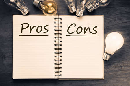 pros: Pros and Cons text on notebook with many light bulbs