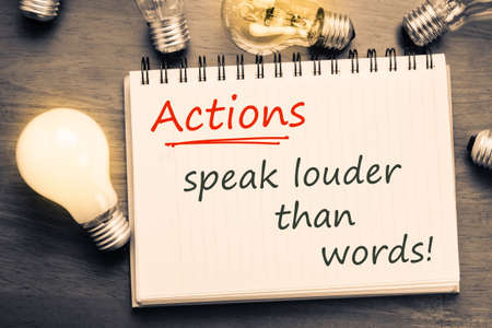 louder: Actions Speak Louder Than Words text on notebook with many light bulbs