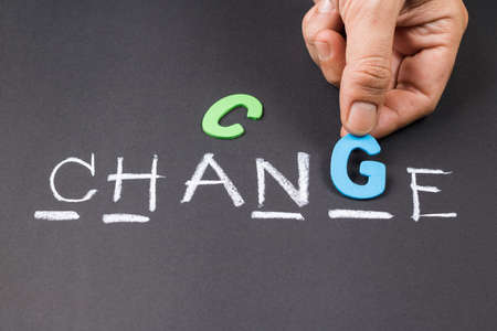 Hand put a wood letter into guess word game for Change concept Stock Photo