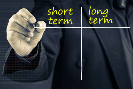 long term: Businessman writing chart of short term and long term on screen Stock Photo