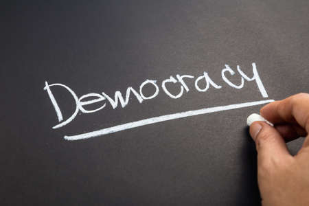 topic: Hand writing Democracy word topic on chalkboard Stock Photo