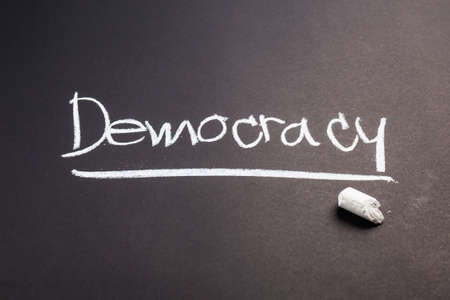 Democracy word topic on chalkboard