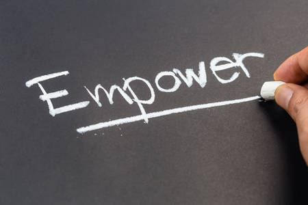 empower: Hand writing Empower word topic on chalkboard Stock Photo