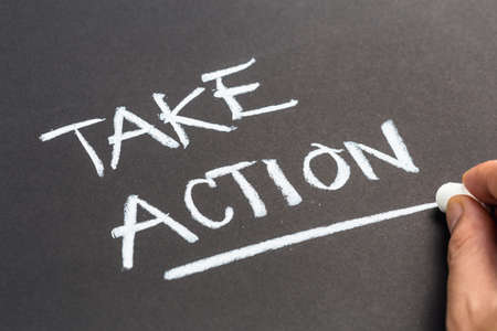 take action: Hand writing text Take Action on chalkboard Stock Photo