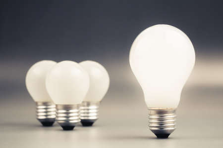 differentiation: Big light bulb glowing with group of small light bulbs on background, leader, differentiation concept