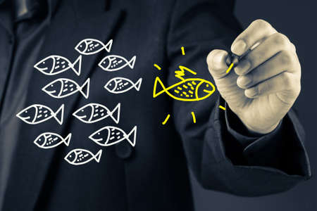 Businessman drawing the yellow fish in opposite direction from the others
