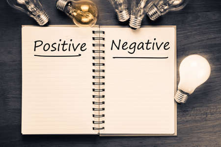 resouce: Positive Versus Negative on notebook with glowing light bulbs
