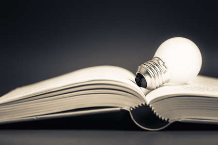 glowing light bulb: Glowing light bulb on opened book Stock Photo