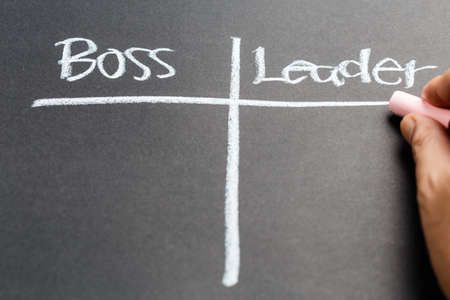 Hand writing Boss versus Leader concept on chalkboard